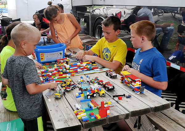 The Olsen children and their friends create a Lego village and vehicles as they play outside the Olsen Custom Farms mobile home Thursday, June 12, 2014. Chad Olsen, a custom harvester from Hendricks, Minnesota, hopes the rain will clear long enough so his crews can continue harvesting wheat in Enid and other locations in Oklahoma. (Staff Photo by BONNIE VCULEK)