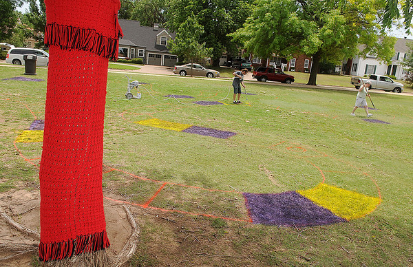"""Colorful crocheted items decorate the trees and light posts at Champlin Park as Paula Nightengale and Andrew Shearon paint a giant Candyland game board on the park's lawn Wednesday, June 4, 2014. Creative Arts Enid is hosting """"Candyland at Champlin Park"""" Friday from 6:30-8:30 p.m. (Staff Photo by BONNIE VCULEK)"""