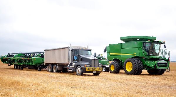 John Deere combines belonging to a custom harvest crew sit idle in a field on S. Oakwood Road as heavy rains stalled wheat harvest Friday, June 12, 2015. (Staff Photo by BONNIE VCULEK)