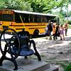The McKinley Elementary School bell appears left as children walk past an Enid Public School bus Wednesday, June 24, 2015. (Staff Photo by BONNIE VCULEK)