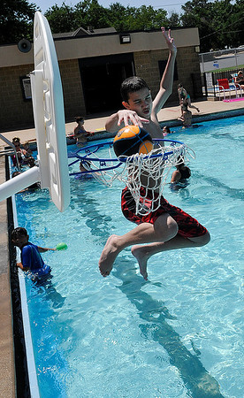 Justus Tyer plays basketball at Champlin Pool Thursday June 16, 2016. The Mesonet site at Breckinridge recorded a second consecutive 100 degree day. (Billy Hefton / Enid News & Eagle)