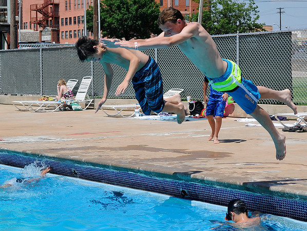 Jason Bryant and Dakota Skaggs dive into Champlin Pool together Thursday June 16, 2016. The Mesonet site at Breckinridge recorded a second consecutive 100 degree day. (Billy Hefton / Enid News & Eagle)