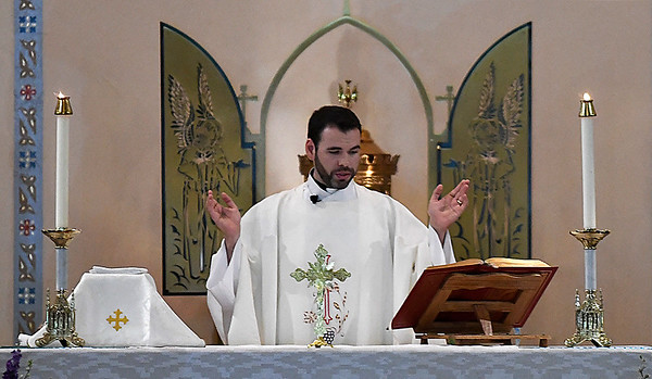 Father Aaron Foshee conducts mass Tuesday June 13, 2017 at St. Francis Xavier Catholoc Church. (Billy Hefton / Enid News & Eagle)