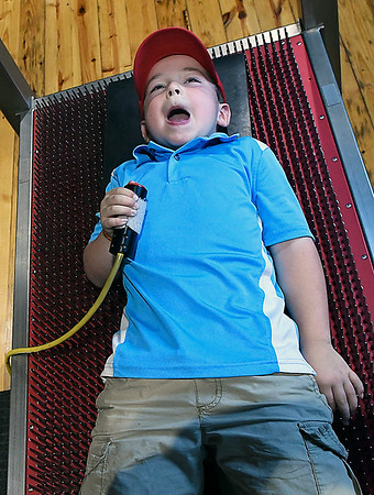 Peter Shepherd reacts as he lays on the bed of nails exhibit at Leonardo's Children's Museum Saturday June 10, 2017 during the grand opening of the new exhibits. (Billy Hefton / Enid News & Eagle)