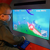 Zachary Haynes flies the flight simulator exhibit at Leonardo's Children's Museum Saturday June 10, 2017 during the grand opening of the new exhibits. (Billy Hefton / Enid News & Eagle)