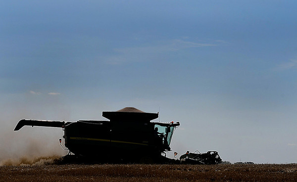 A combine is silhouetted as it harvest a wheat field on north 54th street Wednesday June 7, 2017. (Billy Hefton / Enid News & Eagle)