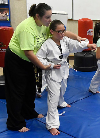 Jennifer Musick gives instruction to Alaina Blakely at the Humanitarian School of Martial Arts Wednesday June 20, 2018. (Billy Hefton / Enid News & Eagle)