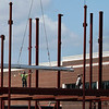 Construction workers help to guide material into place for the Enid High School's new qym and performing arts center Monday JUne 18, 2018. (Billy Hefton / Enid News & Eagle)