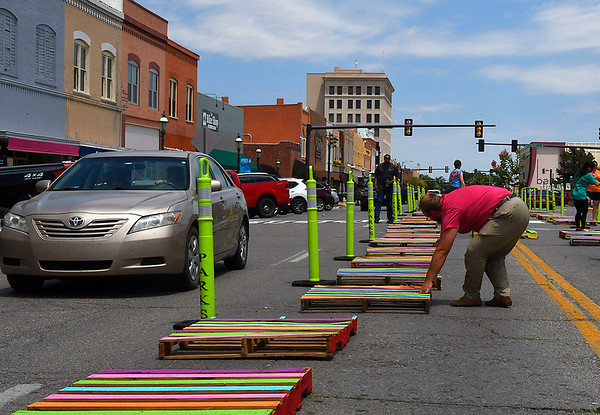"Jay Sharp , of TSET Healthly Living, adjust the width of the ""median"" in the 200 block of west Randolph on the suggestion of passing motorists Thursday June 21, 2018. The ""median"" is part of a Safer Street Simulation with hopes of showing how the street could be safer for pedestrians and motorist. (Billy Hefton / Enid News & Eagle)"