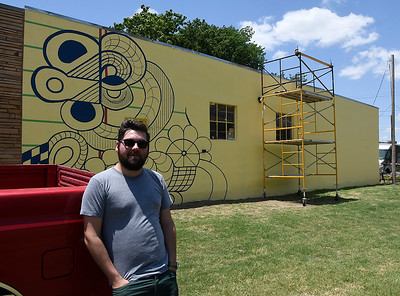 Ben Ezzell stands in front of a partially completed mural on his shop Friday June 15, 2018. The mural is made up of doodles drawn by his late father, David Ezzell. (Billy Hefton / Enid News & Eagle)