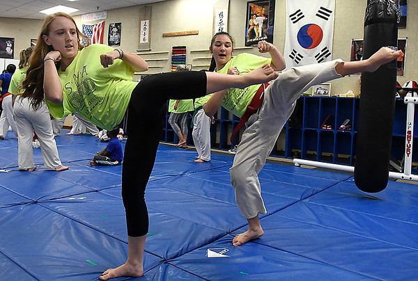 Chole Drennan and Micaiah Musick demostrate kicks at the Humanitarian School of Martial Arts Wednesday June 20, 2018. (Billy Hefton / Enid News & Eagle)