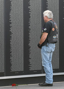 Mike Marxen pauses for a moment os silence after placing a rose at the base of the Vietnam Wall at Woodring Wall of Honor following a fame ceremony Saturday, June 15, 2019. Carry the Flame Across America is an annual Ride from California to Washington D.C. by motorcyclists' traveling to the Vietnam Veterans Monument. The group stopped in Enid at Oklahoma's official Vietnam War Monument to host a Flame Ceremony in honor of the fallen of Vietnam. (Billy Hefton / Enid News & Eagle)