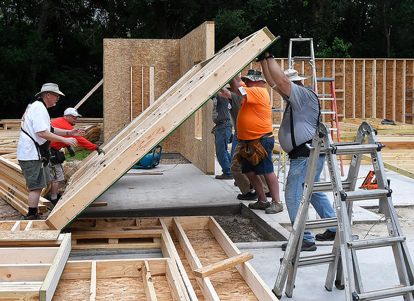 Volunteers for World Mission Builders raise a wall at a house they are building on west Randolph Monday, June 3, 2019. (Billy Hefton / Enid News & Eagle)