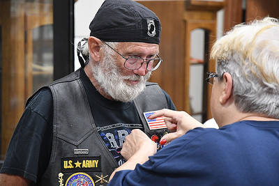 Leroy Halstead watches as Brenda Bingham pins a Vietnam Veteran pin to his vest following a Flame ceremony as part of Carry the Flame Across America Saturday, June 15, 2019. Carry the Flame Across America is an annual Ride from California to Washington D.C. by motorcyclists' traveling to the Vietnam Veterans Monument. The group stopped in Enid at Oklahoma's official Vietnam War Monument to host a Flame Ceremony in honor of the fallen of Vietnam. (Billy Hefton / Enid News & Eagle)