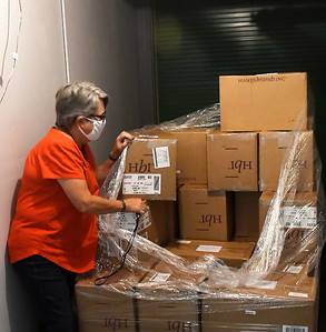 CDSA's Cheri Ezzell stands with a pallet of donated masks that will be distributed to child care workers in northwest Oklahoma. (Billy Hefton / Enid News & Eagle)