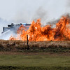 Smoke and flames obscure a brush rig as fire fights a fire in a field along Carrier Road between 54th and 66th streets Monday June, 15, 2020. (Billy Hefton / Enid News & Eagle)
