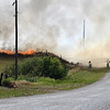 Units from several fire department fight a fire in a field along Carrier Road between 54th and 66th streets Monday June, 15, 2020 trying to keep it from jumping the road. (Billy Hefton / Enid News & Eagle)
