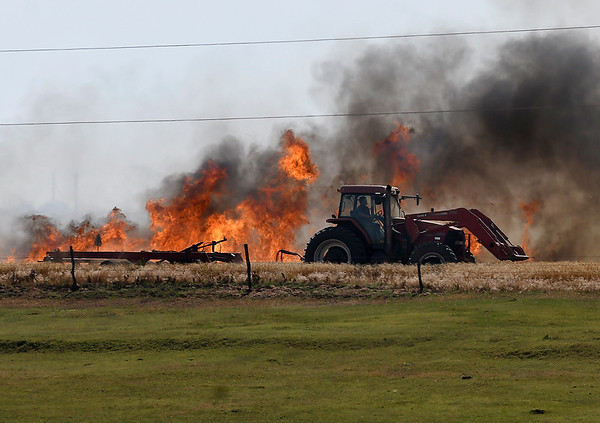 A tractor plows a fire break in a field along Carrier Road between 54th and 66th streets Monday June, 15, 2020. (Billy Hefton / Enid News & Eagle)