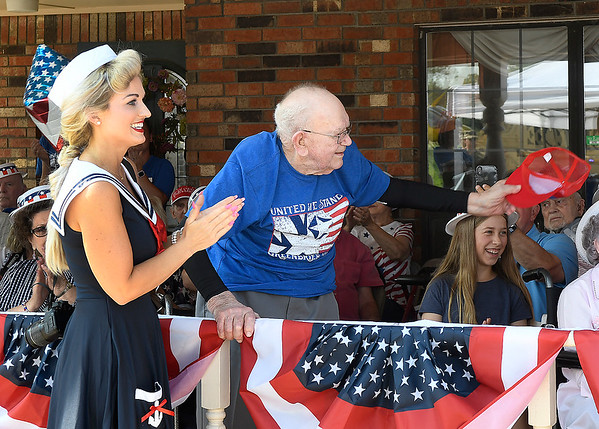 Rex Campbell stands and waves his cap during the playing of the Navy song Achors Aweigh at his 99th birthday celebration Thursday,  June 17, 2021 at Greenbrier Village. (Billy Hefton / Enid News & Eagle)