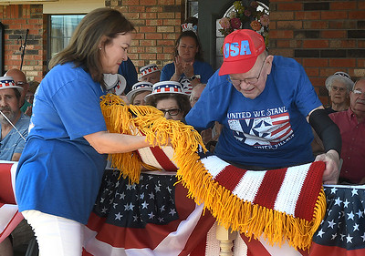 Lori Long presents Rex Campbell with an afghan during his 99th birthday celebration Thursday,  June 17, 2021 at Greenbrier Village. (Billy Hefton / Enid News & Eagle)