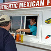 Irma Gonzales explains the selection of sodas to Terry Johnson at the Grab-n-Go food truck in Medford. (Staff Photo by BILLY HEFTON)