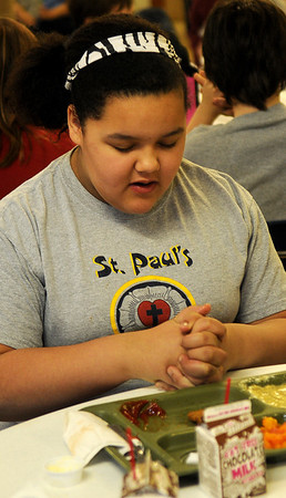 """Miceala Stevenson pauses to pray during lunch at St. Paul's Lutheran School Friday, March 1, 2013. St. Paul's school mission is """"Shaping and Educating Children to live in God's Commands."""" (Staff Photo by BONNIE VCULEK)"""