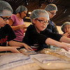 Sebastian Coleman and M.E. Brooks (front, rom left) stack completed meals for Kids Against Hunger at St. Joseph Catholic School Friday, March 15, 2013. Students in pre-K through fifth grade, teachers, and staff packaged more than 10,000 meals during the first day of their Lenten Project. (Staff Photo by BONNIE VCULEK)