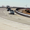 Traffic crosses the recently opened US 81 bridge Monday as a landscaping crew lays sod on the embankment. (Staff Photo by BILLY HEFTON)