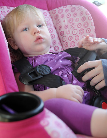 Celeste Spargo buckles her 14-month-old daughter, Abigail Martin, into a child's safety seat Wednesday, March 20, 2013. (Staff Photo by BONNIE VCULEK)