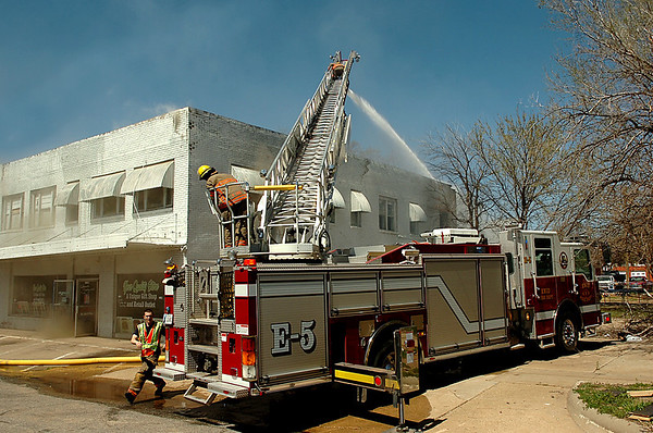 Enid firefighters spray water from a ladder truck onto the building at the intersection of 5th & Broadway Sunday. (Staff Photo by BILLY HEFTON)