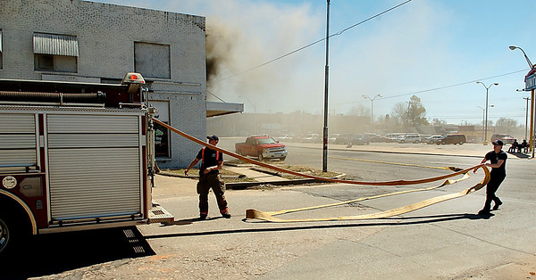 Enid firefighters pull hoses from a truck after arriving on scene of a structure fire at the intersection of 5th & Broadway Sunday. (Staff Photo by BILLY HEFTON)
