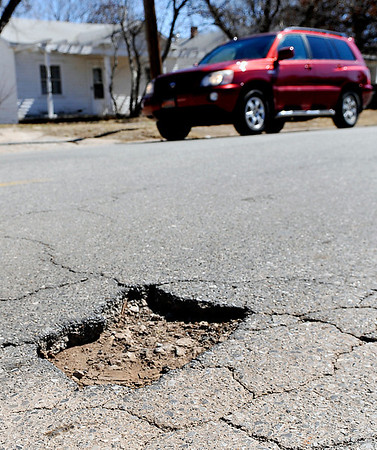 Traffic passes a pothole on north 10th St. Monday. The week of March 11 has been designated fix a pothole week in Enid. Starting Tuesday every member of the street department and the public works department will be out filling potholes. (Staff Photo by BILLY  HEFTON)