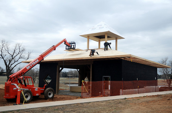 Jerry Tomlinson and Keith Thompson (top, from left) with Henson Construction, mark a chalk line as they install plywood decking on the roof of the new Kiwanis Carousel building at Meadowlake Park North Thursday, March 21, 2013. (Staff Photo by BONNIE VCULEK)