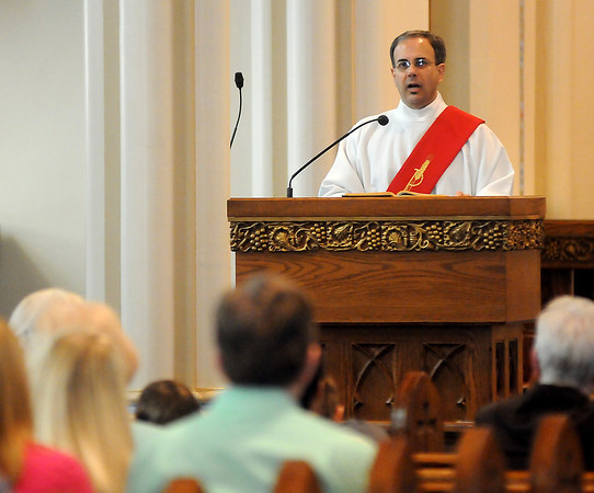 Deacon Tony Crispo shares the scripture reading, John 19:38-42 as Christians observe the passion and death of Jesus at St. Francis Xavier Catholic Church on Good Friday, March 29, 2013. (Staff Photo by BONNIE VCULEK)