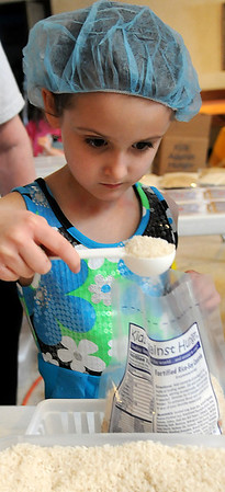 Lillyanna Vculek-Smith scoops rice into a Kids Against Hunger Fortified Rice-Soy Casserole during St. Joseph Catholic School Lenten project at St. Francis Xavier Catholic Church Friday, March 15, 2013. Students in pre-K through fifth grade, teachers and staff packaged more than 10,000 meals on the first day of their event. (Staff Photo by BONNIE VCULEK)