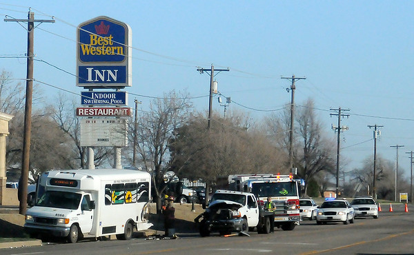 As Enid Firefighters clean up debris (center), Enid Police officers investigate a wreck involving an Enid Public Transportation Authority Enid Transit and an F-350 at the Best Western entrance, 2818 S. Van Buren, Wednesday, March 20, 2013. Enid Police, Enid Fire Department and Life EMS responded to the scene. (Staff Photo by BONNIE VCULEK)