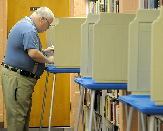 A voter casts his ballot either for or against the Enid Quality of Life Initiative in the Central Christian Church library Tuesday, March 5, 2013. (Staff Photo by BONNIE VCULEK)