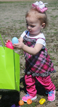 Katie Jo Erford, from Enid, places Easter eggs into her bag during the annual event at Sandbox Learning Center Saturday, March 30, 2013. Employees at the center and Northwestern Oklahoma State University Psychology Club filled thousands of eggs before children arrived. (Staff Photo by BONNIE VCULEK)