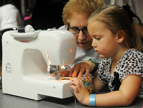 Carleigh (right), 3, learns how to sew a small pillow with the help of Joyce Fales in the new Tinkering exhibit at Leonardo's Discovery Warehouse Friday, March 15, 2013. The Oklahoma Museum Network permanent exhibit was funded by Donald W. Reynolds Foundation.(Staff Photo by BONNIE VCULEK)