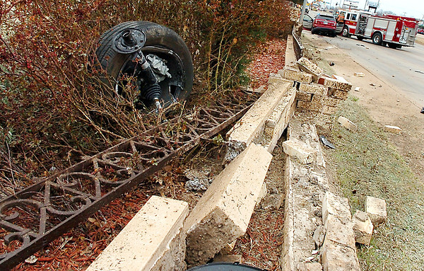 A tire from a suv sits among the shrubs along west Garriott Thursday after the driver hit a brick wall and came to rest in the intersection of Garriott and Hayes. (Staff Photo by BILLY HEFTON)