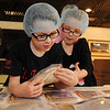 Sebastian Coleman and M.E. Brooks read the ingredients on a packaged meal during St. Joseph Catholic School's Kids Against Hunger Lenten project Friday, March 15, 2013. More than 10,000 fortified rice-soy casseroles were prepared by students, teachers and staff during the first day of their event at St. Francis Xavier Catholic Church's Leven Center. (Staff Photo by BONNIE VCULEK)