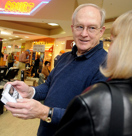 Gene Spillman, with the Enid Amateur Radio Club, shows Donna Wall how to program the new Weather Radio that she won during the second annual Weather and Disaster Preparedness Day at Oakwood Mall Saturday, March 23, 2013. (Staff Photo by BONNIE VCULEK)