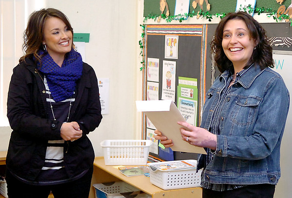 McKinley Elementary teacher, Jennifer Yape (right), smiles after receiving a grant from Enid Public Schools Foundation executive director, Jennifer Fields, Monday. (Staff Photo by BILLY HEFTON)