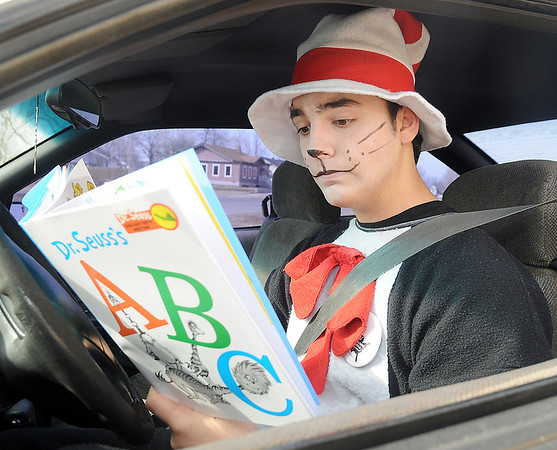 """The Cat In The Hat, portrayed by Evan Chermack, reads Dr. Seuss's ABC as he waits inside his car for children to arrive at Loaves & Fishes Wednesday, March 6, 2013. The Enid Education Association sponsors the annual """"Spot the Cat"""" activities for area school children. (Staff Photo by BONNIE VCULEK)"""