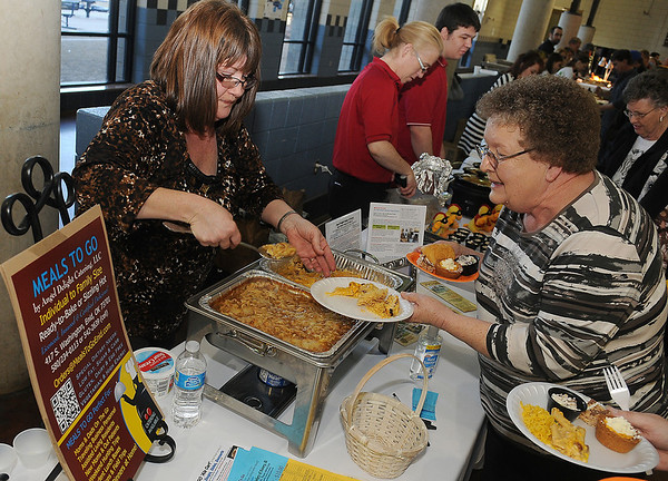 Gayla Crum, with Meals to Go by Angel Delight Catering, LLC, serves two different casseroles to guests during the Festival of Flavor at the Enid High School Food Court Tuesday, March 12, 2013. Proceeds raised during the Rotary event helps purchase technical equipment for Enid Public Schools and for worldwide polio eradication. (Staff Photo by BONNIE VCULEK)