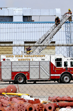 An Enid firefighter descends from the roof of GEFCO, Inc. Wednesday afternoon. (Staff Photo by BILLY HEFTON)