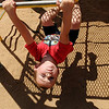 Daniel Almond braves the heat as he swings on a monkey bar at Meadowlake Park North Tuesday, July 24, 2012 in Enid, Okla. (AP Photo/Enid News and Eagle, Bonnie G. Vculek)