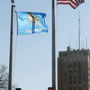Broadway Tower looms in the background (right), as a brisk, cold wind unfurls the flags in downtown Enid Wednesday, March 20, 2013. (Staff Photo by BONNIE VCULEK)