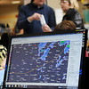 A computer screen (front) displays the current weather radar as Gene Spillman shows Donna Wall how to program her new weather radio during the second annual Weather and Disaster Preparedness Day at Oakwood Mall Saturday, March 23, 2013. (Staff Photo by BONNIE VCULEK)