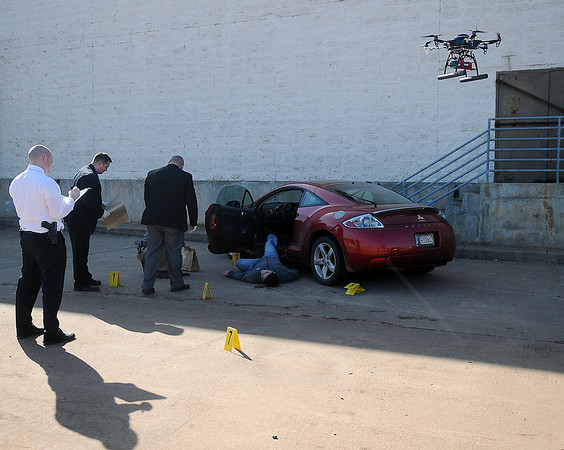 A remote helicopter camera (right), operated by Jack Quirk from KJ Productions, films a new Enid Police Department recruitment video at the vacant Homeland location Wednesday, March 13, 2013. (Staff Photo by BONNIE VCULEK)